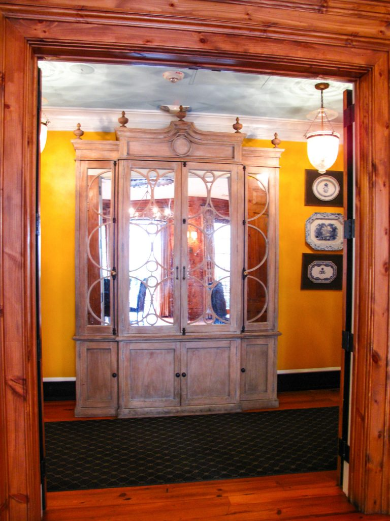 Large wooden hutch in yellow upstairs hallway.