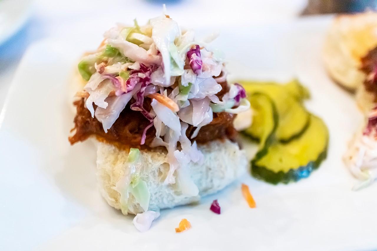 Vegetable slaw on pork slider, on a biscuit with pickles on the side.